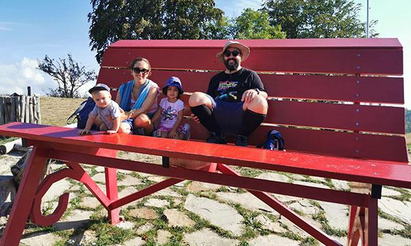 famiglia seduta su una panchina gigante rossa