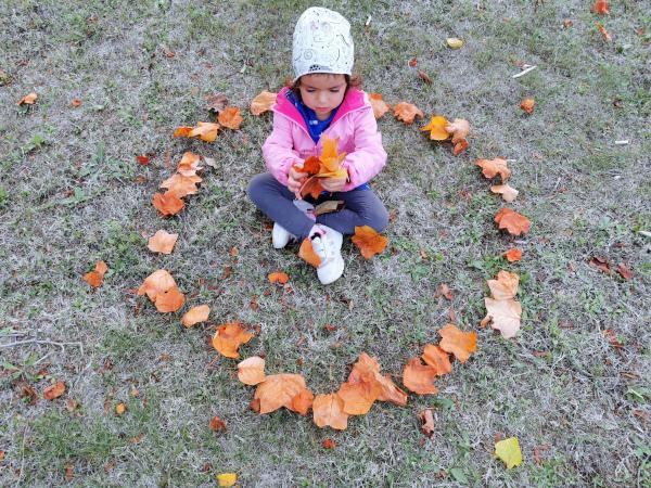 bimba in un cerchio di foglie che gioca con le foglie cadute