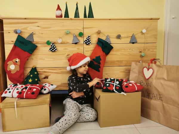 bimba intorno ai regali e alle decorazioni natalizie