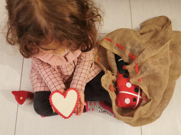 bimba tiene in mano un cuore di feltro con sacca dei regali