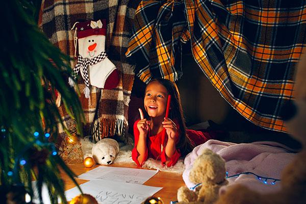 bambina sotto una tenda fatta con una coperta, atmosfera natalizia