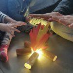 mani che si scaldano sul fuoco di carta