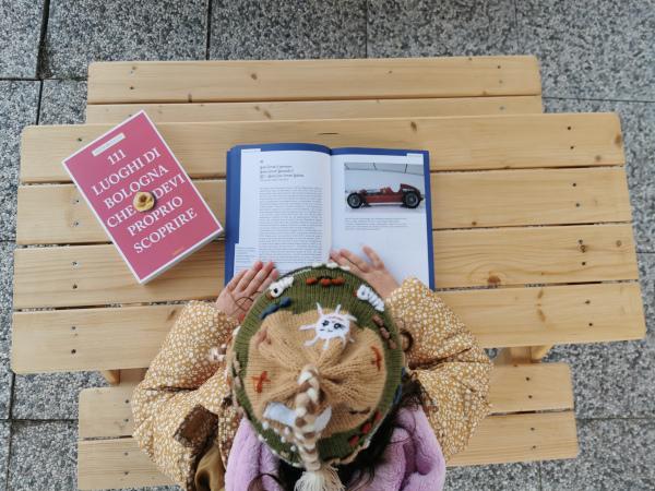 bimba che legge la guida ai luoghi geniali, con accanto il libro sui 111 luoghi di Bologna