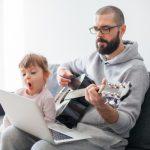 papà suona la chitarra con bimba davanti al computer