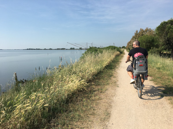 babbo in bici con bimba accanto al mare