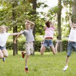 bambini che saltano in mezzo al verde