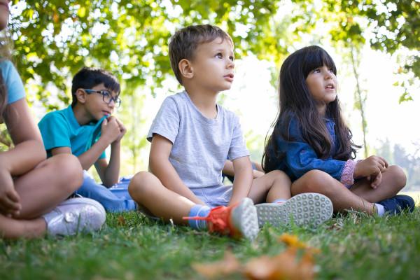 bimbi ascoltano storia sul prato