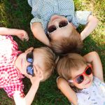 bimbi con occhiali da sole sull'erba