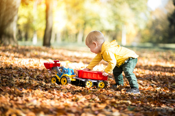 bimbo gioca con trattore e foglie